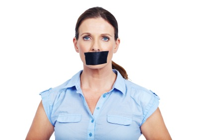 Portrait of serious woman with tape on her mouth - conceptual